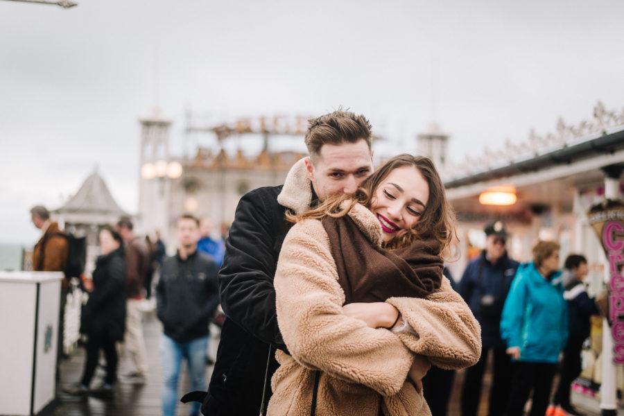 Coppia che si abbraccia sul Brighton Pier in mezzo alla gente, sotto alla pioggia