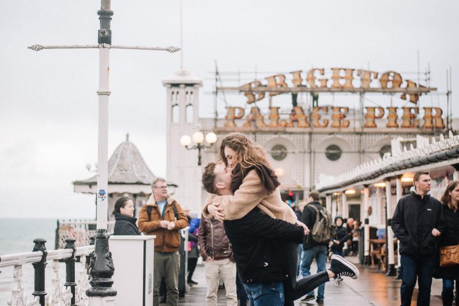 Coppia che si bacia sul Brighton Pier in mezzo alla gente, sotto alla pioggia