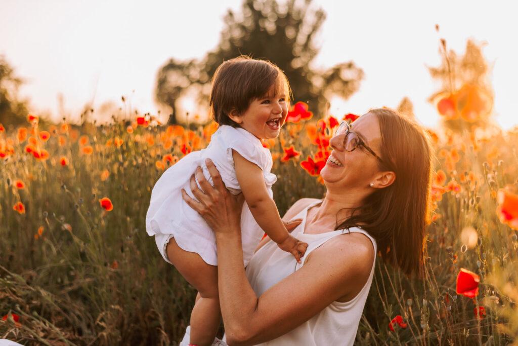 mamma che alza sua figlia tra i papaveri al tramonto