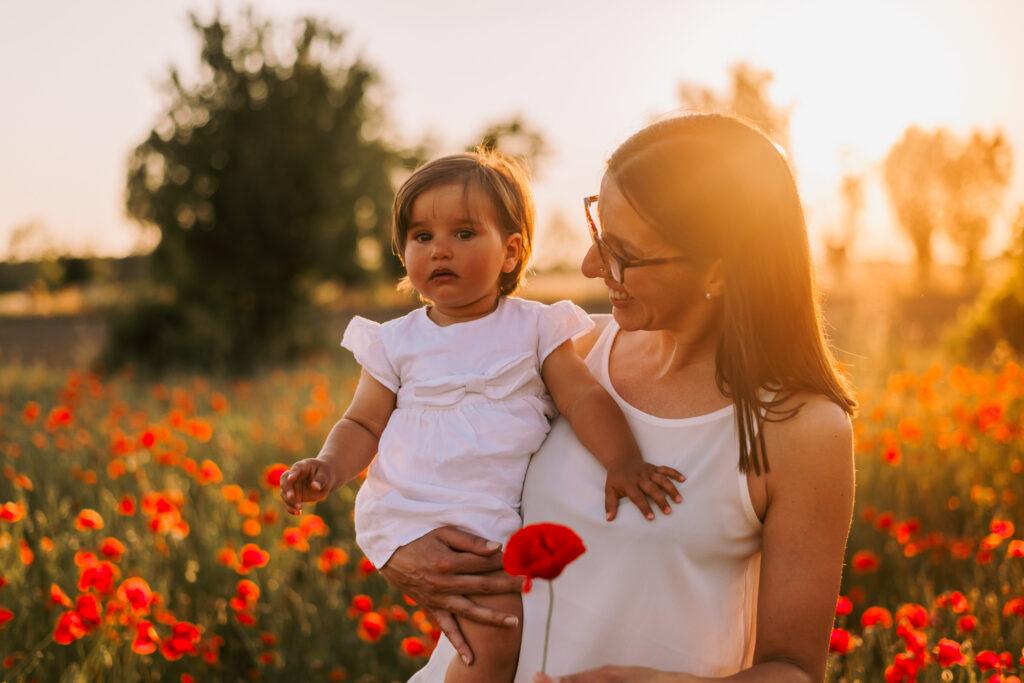 mamma e figlia che si guardano al tramonto tra i papaveri sessione fotografica